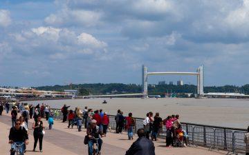 Piéton marchant le long des quais avec le pont Chaban en arrière plan